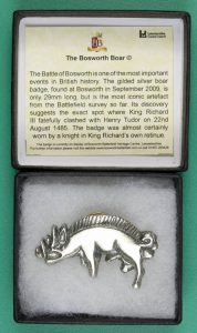 A pewter copy of the boar badge in its box.