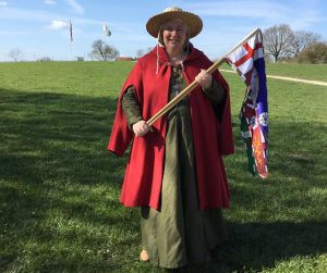 Female costumed guide with a flag